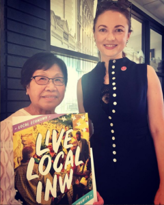 Toi stands with Live Local poster and SIMBA Founder Mariah McKay
